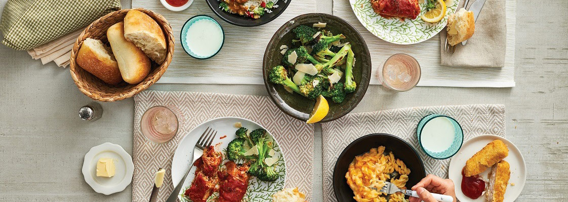 Weeknight dinner table with plates of cabbage rolls chicken and broccoli
